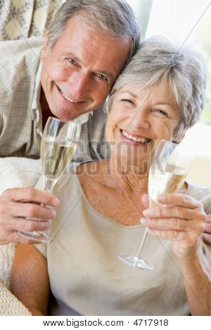 Couple In Living Room Drinking Champagne And Smiling