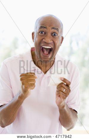 Man met Winning Lottery Ticket opgewonden en glimlachen