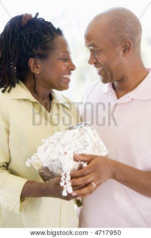 Husband And Wife Holding Gift Smiling