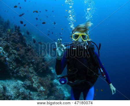 Underwater shoot of a woman diving with scuba by coral reef and showing ok signal