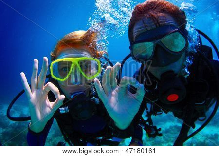 Underwater shoot of a couple diving with scuba and showing ok signal