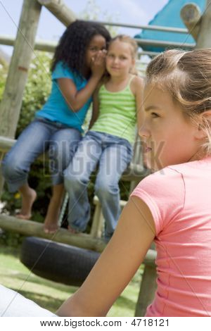 Two Young Girl Friends At A Playground Whispering About Other Girl In Foreground