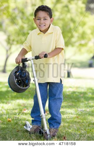 Young Boy Outdoors On Scooter Smiling