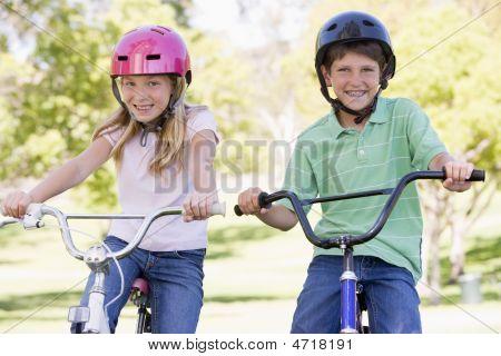 Bruder und Schwester im Freien auf Fahrrädern lächelnd