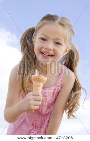 Jovencita al aire libre comer helado y sonriendo
