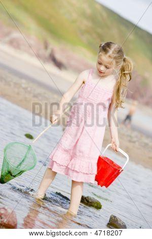 junges Mädchen am Strand mit Net und Eimer