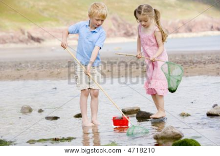 Brother And Sister At Beach With Nets And Pail