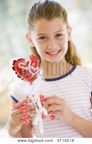 Young Girl On Valentine's Day Holding Love Themed Balloon Smiling