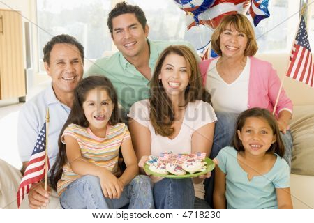 Family In Living Room On Fourth Of July With Flags And Cookies Smiling