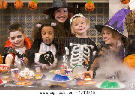 Quatro jovens amigos e uma mulher no dia das bruxas comer guloseimas e sorrindo