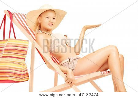 Woman sitting on a sun lounger and gesturing with a hand, isolated on white background