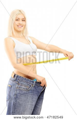 Smiling weightloss woman in old pairs of jeans measuring her waist after diet, isolated on white background