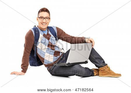 Smiling handsome guy sitting on a floor with laptop and looking at camera isolated on white background