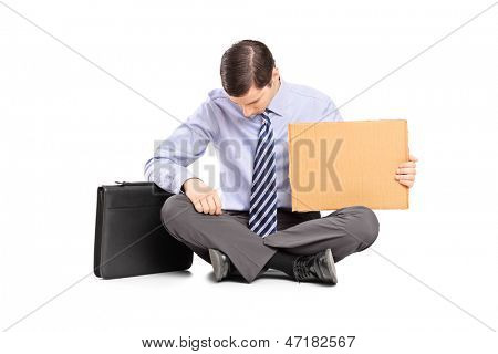 Bankrupted businessperson begging with a piece of cardboard, isolated on white background