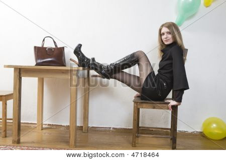 Young Blond Woman Sitting On Chair At Table Put Her Legs On Table. Bag Standing On Table. Room Decor