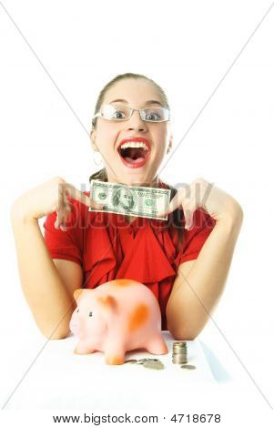 Excited Woman Puttting Money Into Her Piggy Bank