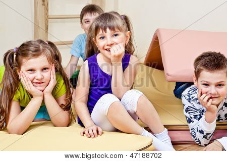 Primary school students sitting on tumbling mats
