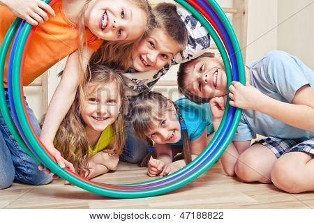 Five cheerful kids looking through hula hoops