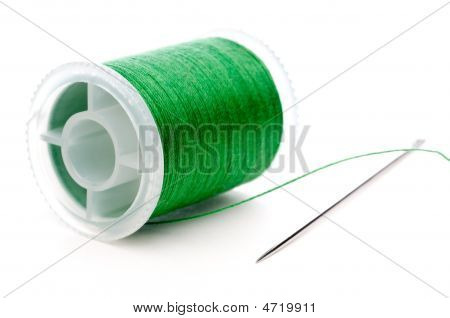 A Spool Of Green Thread And A Needle