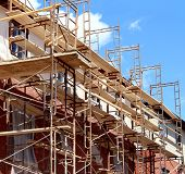 pic of scaffolding  - Residential construction in the process of being built as a real estate structure with metal scaffolding as a business symbol of economic investment rise with financial growth in a healthy economy - JPG