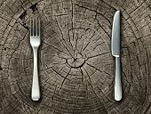 stock photo of primite  - Natural food concept and organic eating healthy lifestyle idea with a silver fork and knife on a cut tree stump log representing raw food and rustic country cooking and traditional cuisine - JPG