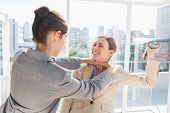 stock photo of strangle  - Businesswoman strangling her partner holding a shoe in bright office - JPG