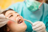 foto of hand drill  - Dentist doing a dental treatment on a female patient - JPG
