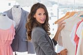 stock photo of blazer  - Fashion woman choosing clothes and looking at the camera - JPG