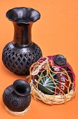 image of mezcal  - Assortment of typical Mexican handicrafts made of black clay from Oaxaca Mexico on orange table - JPG