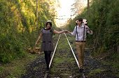 stock photo of propose  - Retro hip hipster romantic love couple walking vintage train tracks - JPG