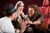 stock photo of seer  - Aggressive fortune tellers taking money from man in hat - JPG