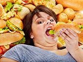 foto of high calorie foods  - Overweight woman holding hamburger - JPG