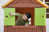stock photo of playgroup  - Small child playing with window in a toy playhouse in an yard or an outdoor playground - JPG