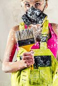 stock photo of respirator  - Female construction worker wearing respirator holding paint brush - JPG