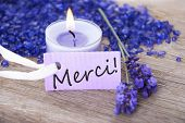 stock photo of gratitude  - a purple label with the french word merci which means thanks and a recreational background