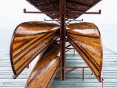 pic of pontoon boat  - Wooden rowboat is hanging in the boat house in the early morning with fog - JPG