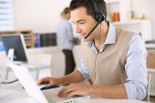stock photo of helpdesk  - Portrait of consultant on the phone with headset - JPG