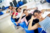 image of gym workout  - group of people at the gym smiling an doing abs exercises - JPG