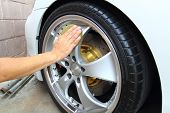 stock photo of suds  - Hand wipe a microfible coated wheels car - JPG