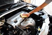stock photo of hand truck  - Hand wipe microfible a Car Engine background - JPG