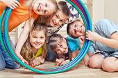 stock photo of gymnastic  - Five cheerful kids looking through hula hoops - JPG