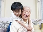 stock photo of 70-year-old  - grandpa and grandson having fun at home - JPG