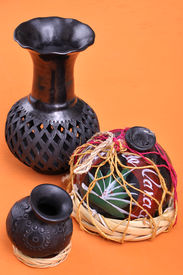 stock photo of mezcal  - Assortment of typical Mexican handicrafts made of black clay from Oaxaca Mexico on orange table - JPG