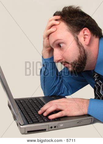 Man Frustrated Looking At Laptop Computer