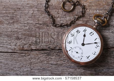 Old Gold Pocket Watch On A Chain On An Old Wooden