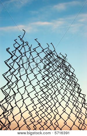 Broken Chainlink Fence Against Sky