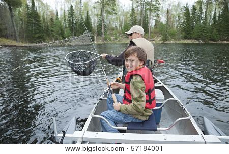 A Young Fisherman In A Canoe Smiles Seeing Walleye Netted