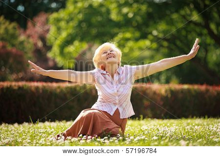 Gladness. Meditation. Mature Pleased Woman Relaxing With Outspread Arms