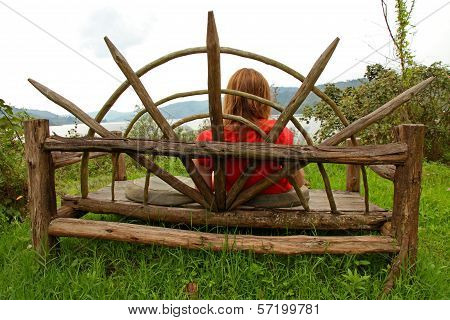 Woman Resting On A Large Wooden Bench