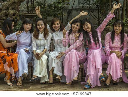 Seven Joyful Female University Seniors Dressed In Ao Dai.